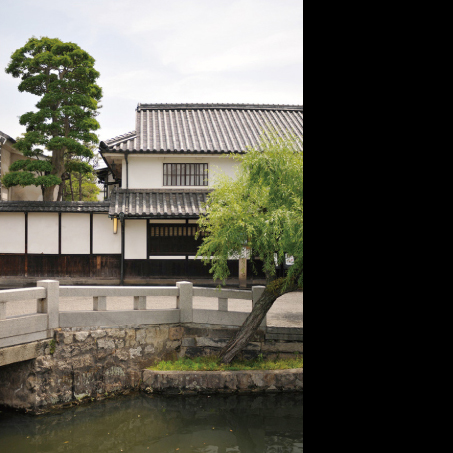 Ryokan Kurashiki peeks out from behind a willow tree along the canal.