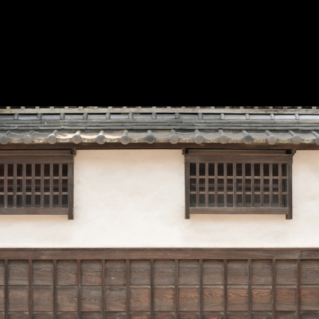 Details of the wooden windows, lime washed wall, and tiled roof of one of the town's oldest storehouses.